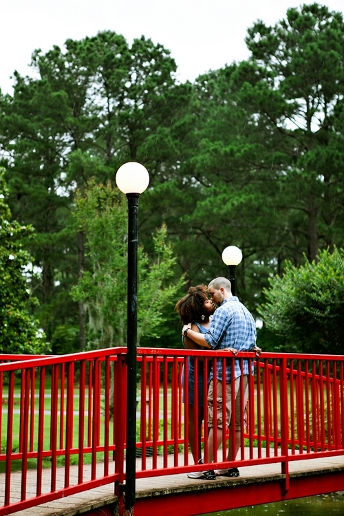 couple kissing on red bridge in the rain