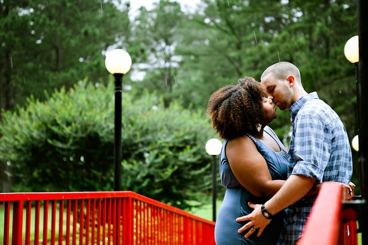 couple kissing on a red bridge in the rain