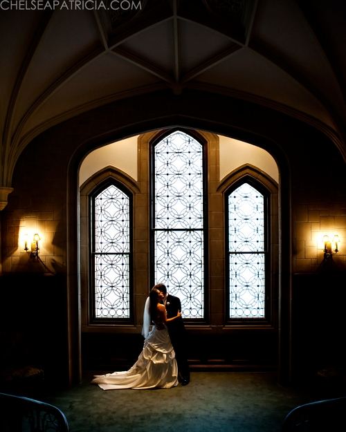 bride and groom in front of grand windows